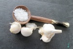 Salt in a wooden spoon with garlic